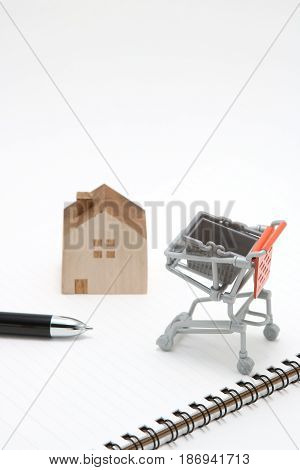 Shopping cart and house on white background. Buying new house, real estate and home mortgage concept.