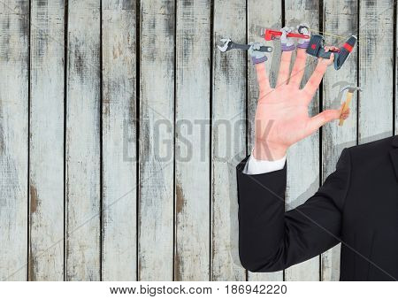 Digital composite of Hand with hands with tools on the fingers. Wood background
