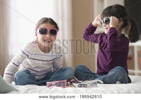 Playful girls trying on sunglasses