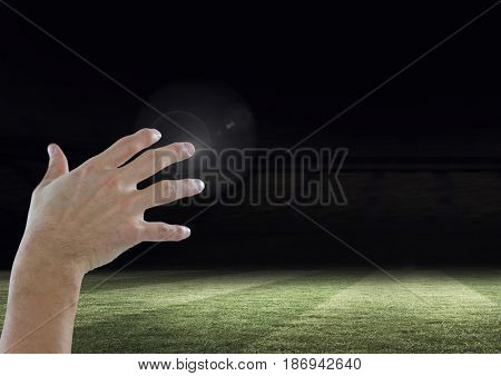 Digital composite of Hand touching  air with sports field