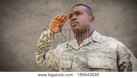 Digital composite of Soldier saluting against brown background with grunge overlay