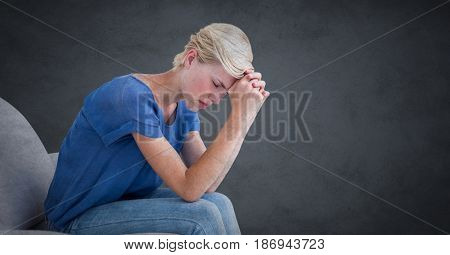 Digital composite of Woman sitting on couch with head on hands against grey background with grunge overlay