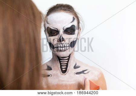 Make-up artist make the girl halloween make up on white background. Halloween face art.