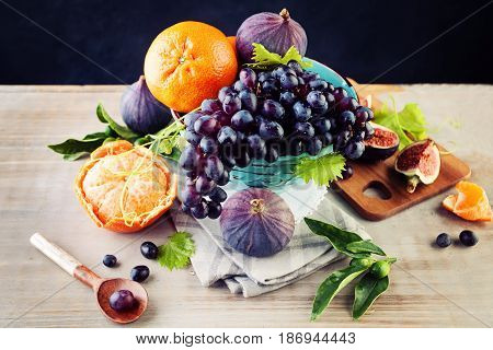 Stilllife with Organic Food. Fresh Fruit Background with Grape Orange Figs and Plum with Green Leaves