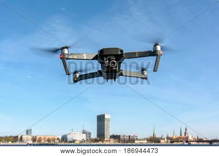 Close up of small drone in blue sky who capturing the video and in background city view