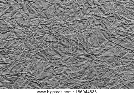 the old crumpled sheet of paper of gray color for the abstract textured background and for wallpaper