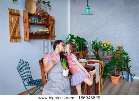 Mother daughter bio. Young beautiful mother kisses her daughter.