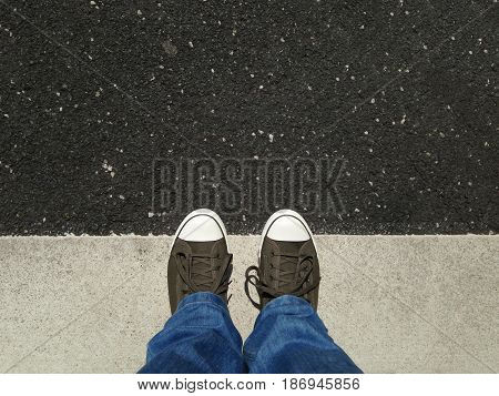 foot selfie or feet in canvas shoes standing on asphalt aligned with road markings