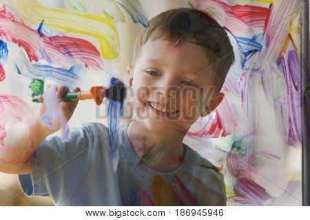 Caucasian boy painting on glass