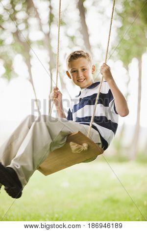 Caucasian boy swinging on swing