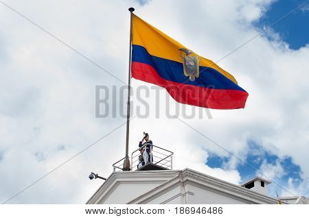 Quito, Ecuador - October 27, 2015: An unidentified man on top of the Presidential palace during the weekly changing of the guards with a huge ecuadorian flag.