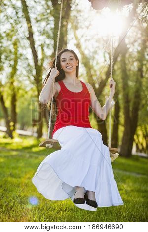 Caucasian woman swinging on swing