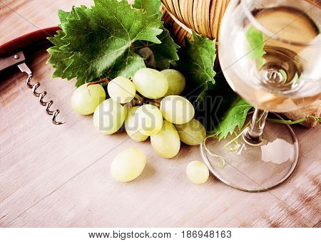 Wine Glass Grape and Grapevine with Green Leaves on Rustic Wooden Board Background