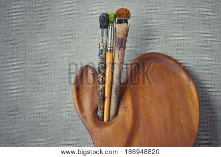 Wooden palette and artist's brush against the backdrop of a canvas stretched over a frame