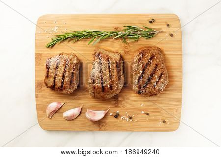 Three slices of grilled meat, beef fillets, shot from above on a wooden board with a sprig of rosemary, garlic cloves, salt, and pepper