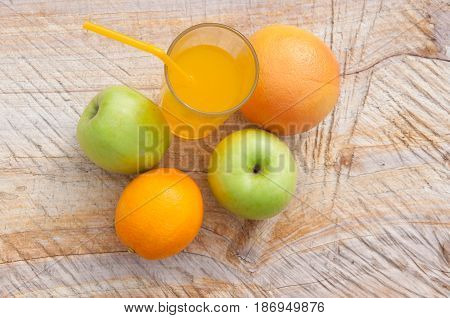 Composition of fresh juice in transparent glass and green apples oranges on wooden background. Top view