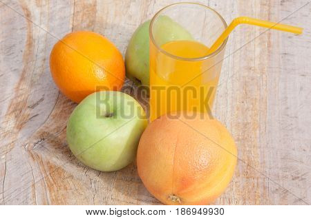 Healthy food. Fruits and fresh orange juice in glass with cocktail tube on wooden background
