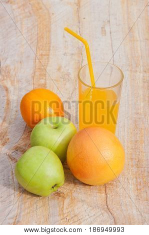 Vertical photo of healthy food apples oranges and juice in glass with cocktail tube on wooden background