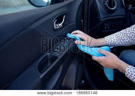 Hand with a microfibre cloth cleans the interior of the car close up
