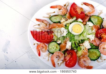Salad with vegetables and shrimps in a white dish. On a light background. Horizontal shot.