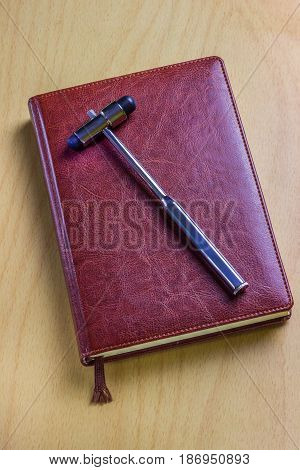 Leather notebook of the neurologist on the table with a medical tool