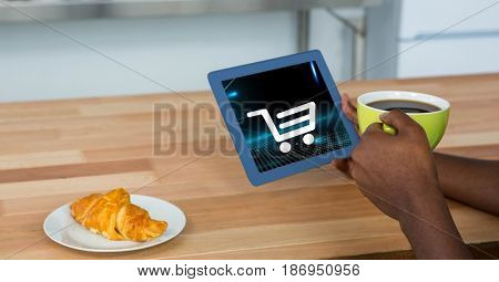 Digital composite of Cropped image of person holding digital tablet with shopping cart icon on screen while having coffee