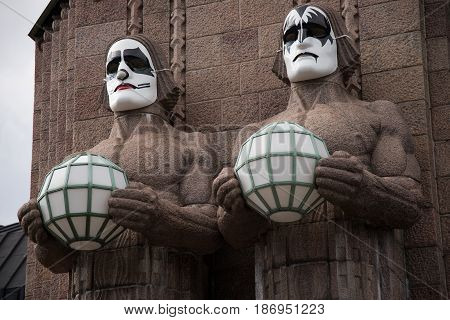 HELSINKI, FINLAND - MAY 1: Iconic stone men statues by the side of the entrance to the Helsinki Central Railway Station decorated as wearing heavy rock band Kiss masks during First of May celebrations May 1, 2017 in Helsinki, Finland.
