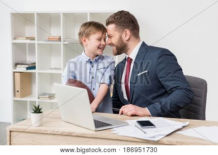 Businessman With His Son At Table In Office
