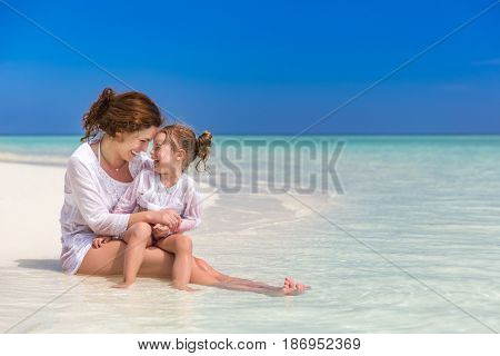 Mother and little daughter playing on sunny beach
