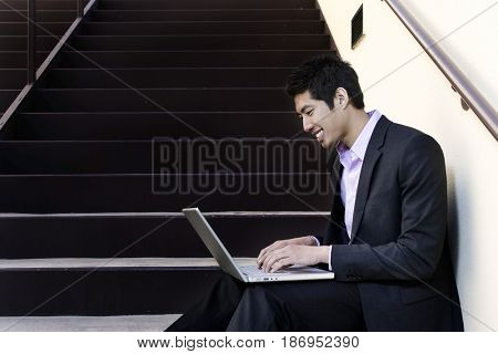 Asian businessman sitting on steps using laptop