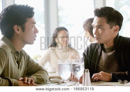 Asian men talking in restaurant