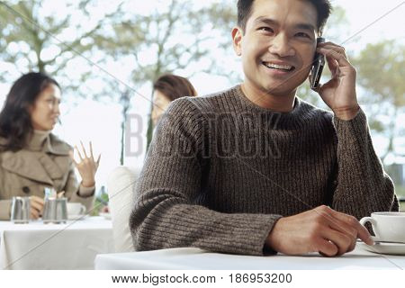 Asian man talking on cell phone in cafe