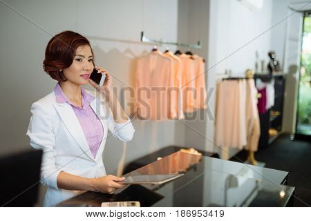 Pretty Vietnamese boutique owner calling on the phone