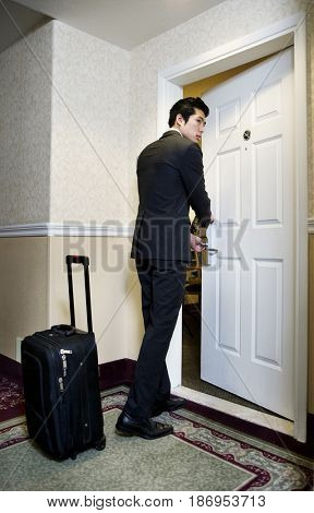 Asian businessman entering hotel room