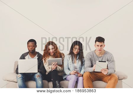 People working with gadgets, addiction concept, copy space. Friends sitting on sofa indoors and working on project