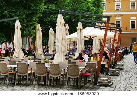 CLUJ-NAPOCA ROMANIA - MAY 7 2017: Turists eat drink and socialize with friend and family at an outdoor terrace.