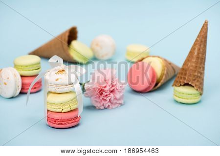 Colorful Macarons Tying With White Ribbon For Gift On Blue Surface. Still Life Of Macarons With Flow