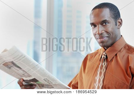 African American businessman reading newspaper in office