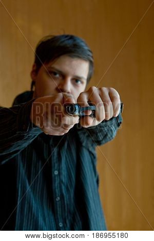 Armed man pointing a gun in a camera