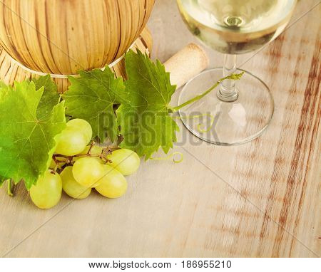 Wine Grape and Grapevine with Green Leaves on Rustic Wooden Board Background