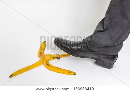 Businessman stepping on banana peel on white - business risk concept
