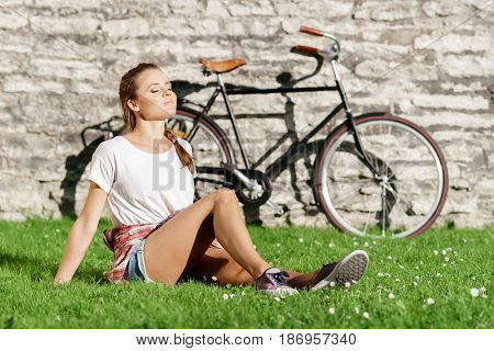 Young, beautiful attractive hipster girl relaxing in park. Holiday, vacation, traveling concept.