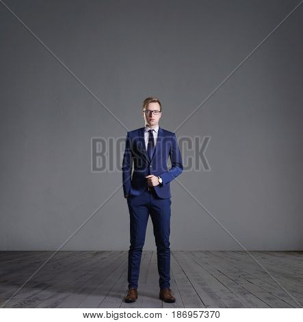 Businessman standing in front of a grey wall. Business, office, concept.