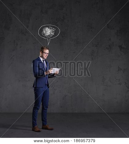 Businessman with a tablet gadget. Black background with copyspace. Business and office technology concept.