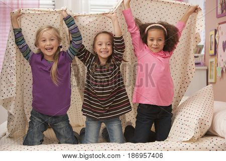 Smiling girls playing underneath bed sheet