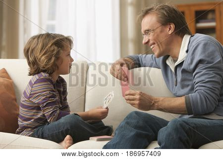 Caucasian father and son playing cards