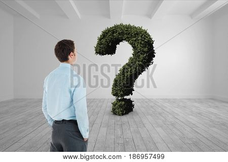 Digital composite of Businessman looking at question mark made of plants