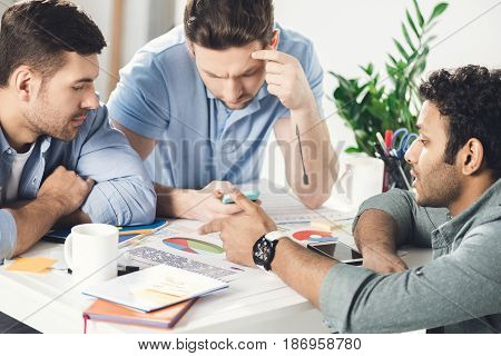 Three Young Businessmen Sitting At Table And Working On New Project Together, Business Teamwork Conc