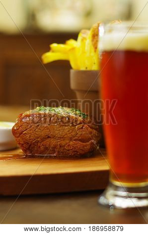 Close up of a well-done grilled marinated beef flank steak with a blurred french fries and glass of beer, on wooden board.