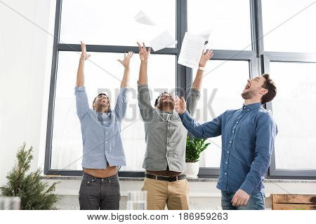 Cheerful Young Businessmen Triumphing And Throwing Papers In Office, Business Teamwork Concept